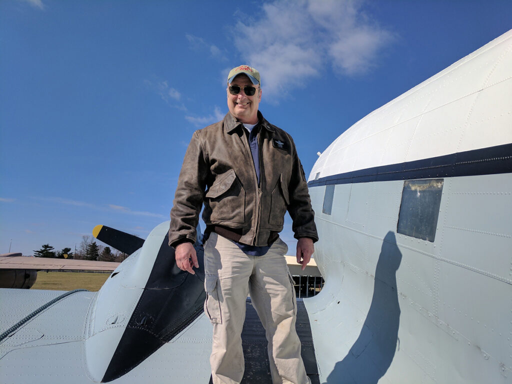 Pilot DJ Doran standing on the wing of a DC-3